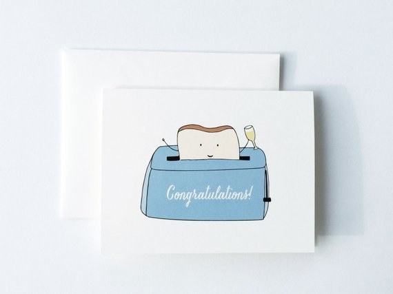 "greet card with an illustration on it of a toaster that says ""Congratulations"" on it with a piece of toast popping out of it holding a champagne glass"