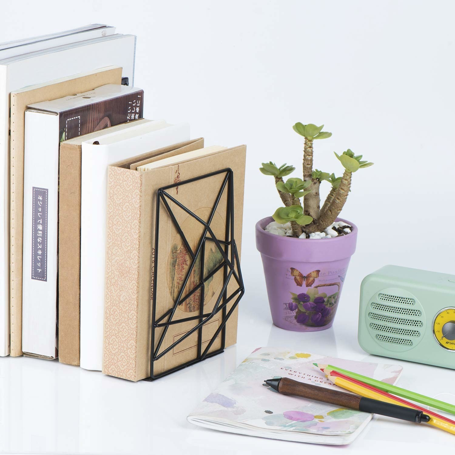 a black wire geometric bookend holding up various books