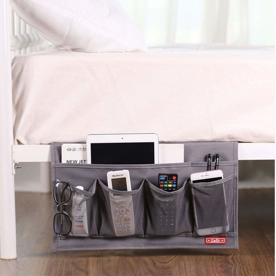 The caddy holding glasses, electronics, and remotes on the side of a bed