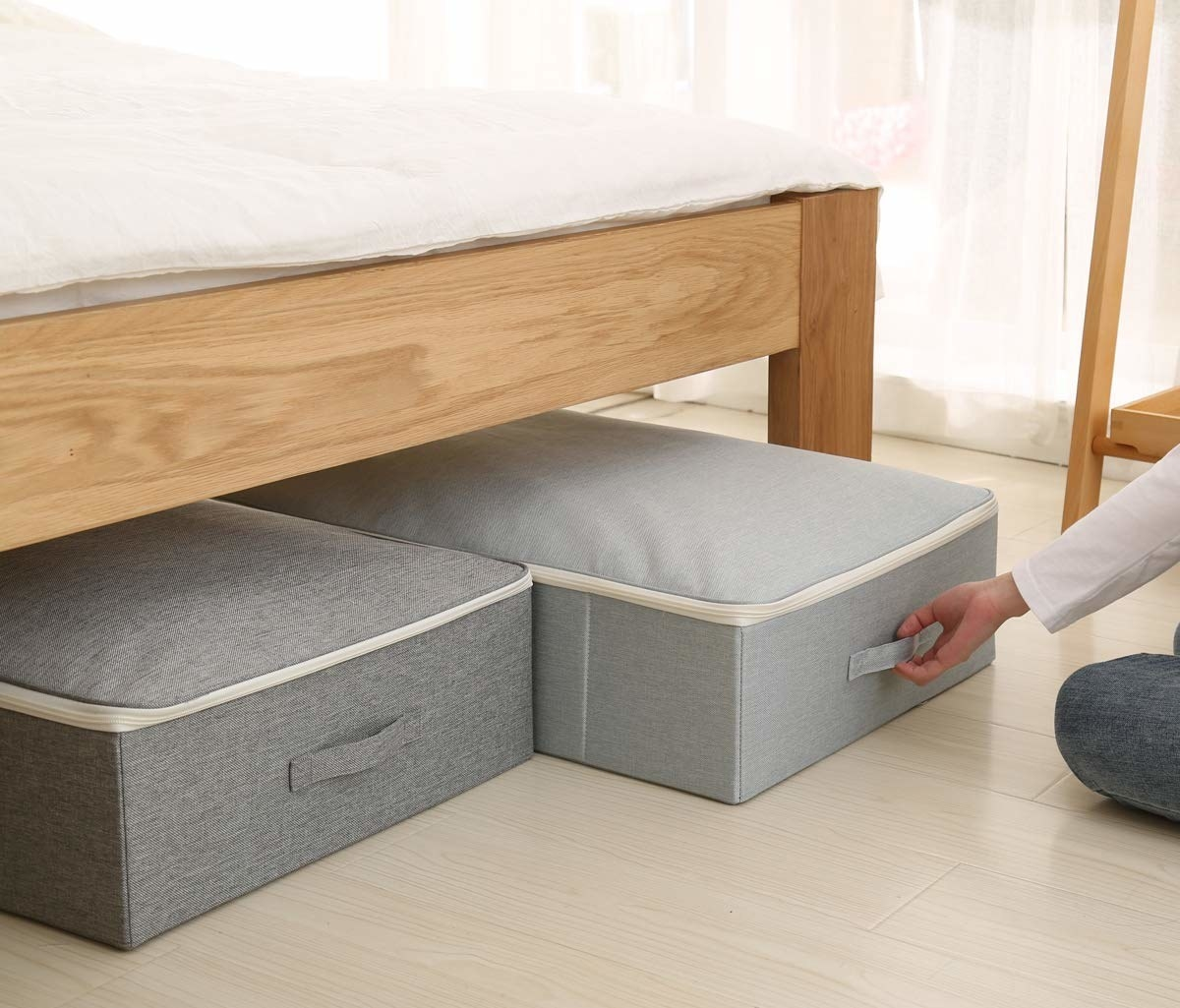 A person sliding the storage box under a bed