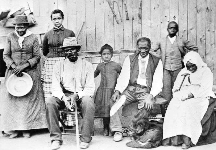 Harriet Tubman, on the far left holding a pan, poses with a group of people whom she helped escape from slavery in the late 19th century.
