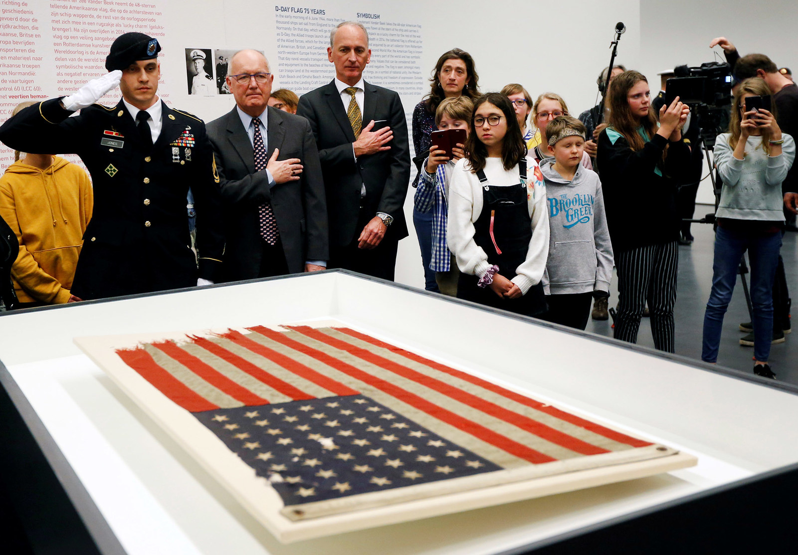 US Ambassador Pete Hoekstra unveils an American flag from Navy ship LCC 60 that led the US invasion fleet at Normandy's Utah Beach, in Rotterdam, Netherlands, on Feb. 4.