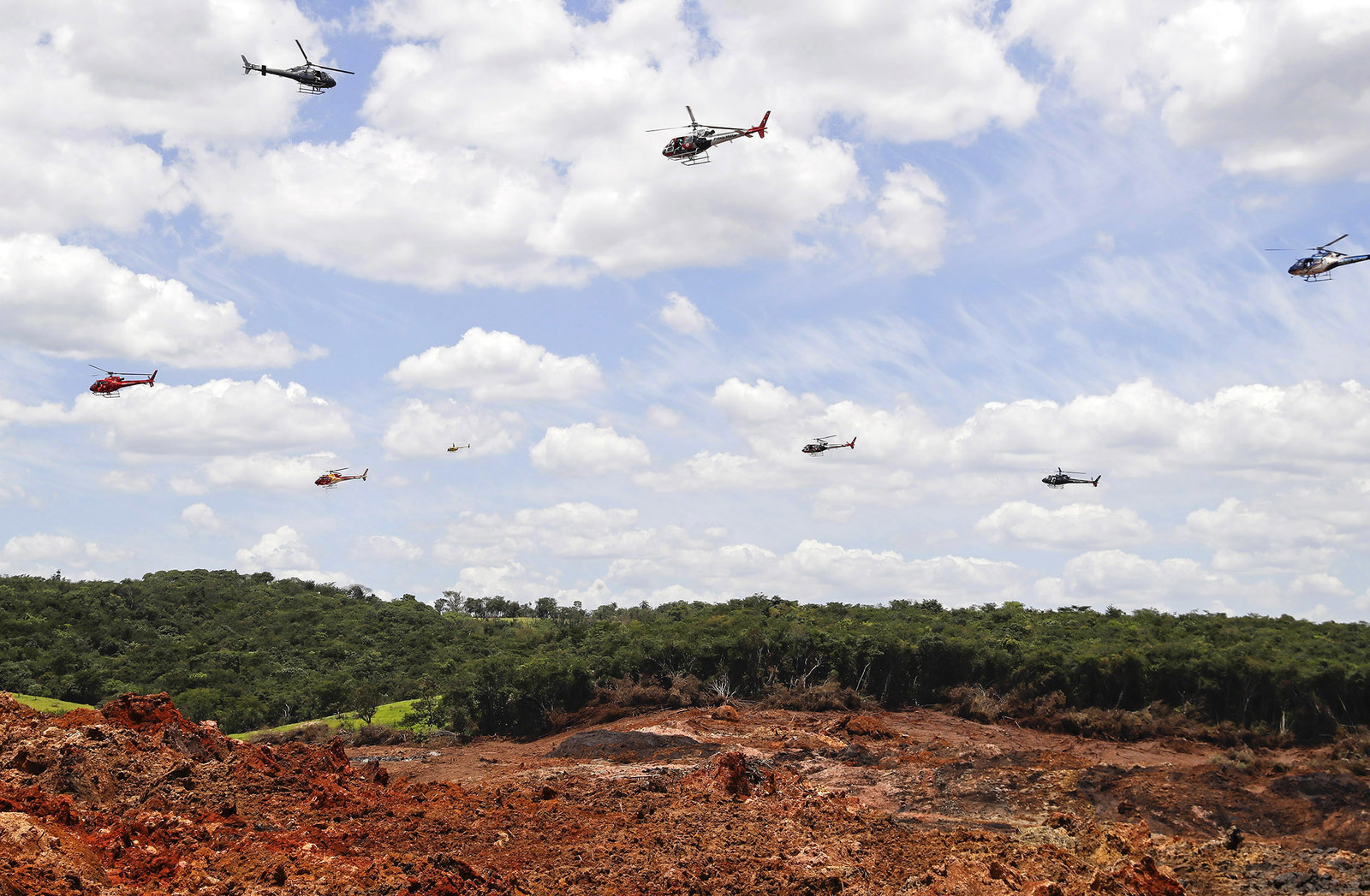 Helicopters hover over an iron ore mining complex to release thousands of flower petals paying homage to the dozens of victims killed and scores of missing after a mining dam collapsed there a week ago, in Brumadinho, Brazil, on Feb. 1.