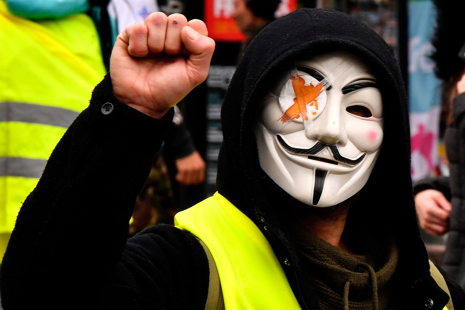 """A """"Yellow Vest"""" supporter wears a Guy Fawkes mask with a bandaged eye representing those protesters injured by the French police, as he takes part in a 'Day of strikes' in Bordeaux, France, on Feb. 5."""