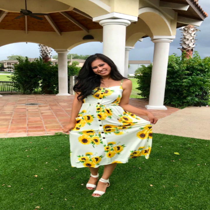 A reviewer wearing the dress in sunflower print