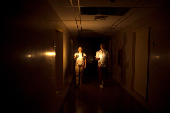 Relatives of a patient walk in the darkened hall of a clinic with a candle lighting the way during a power outage in Caracas on March 7.