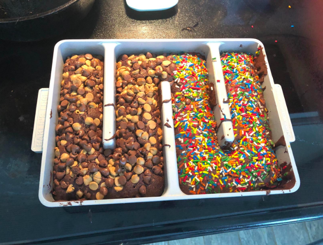 The pan, which has barriers in the middle that almost make it look like a maze shape. This reviewer has covered half the brownies with chocolate and peanut butter chips and the other half with sprinkles