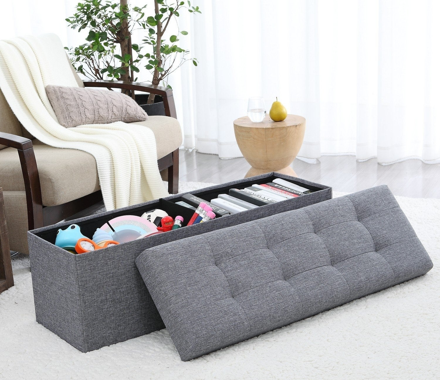 """The bonus? It comes in three sizes and is upholstered in a linen fabric, so it's super durable. The tufted, cushioned top makes it a great option for extra seating.Promising review: """"This is a heavy and sturdy collapsible bench unlike others I've had before. I'm very impressed honestly. The top is thick and cushioned and the bench can easily hold my weight. Color is true to photo. It comes with an optional divider, if you'd like to divide the inside space."""" —CheyNickoleGet it from Amazon for $33.99+ (available in three sizes and eight colors)."""
