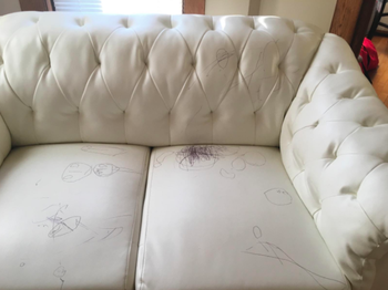 white leather couch with tons of pen scribbles on it