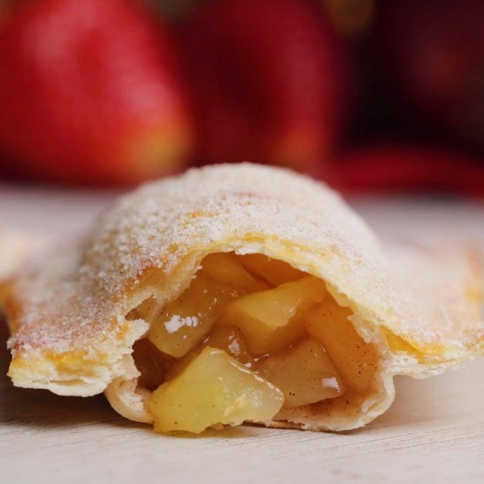 Rendimento: 8-10 unidadesVocê vai precisar de:2 xícaras de maçãs descascadas e picadas¼ xícara de chá de açúcar refinado¼ de colher de chá de canela em pó½ colher de chá de essência de baunilha1 colher de sopa de amido de milhoÁgua para fechar as tortinhas1 rolo de 350g de massa fresca para pastel1 ovo batida2 colheres de sopa de manteiga sem sal derretida⅓ xícara de açúcar refinado para cobrir1 colher de chá de canela em pó para cobrirMode de preparo:1. Preaqueça o forno à 180°C.2. Em uma tigela média, misture a maçã, o açúcar, a canela, a essência de baunilha e o amido. Leve ao micro-ondas por 4 minutos, até as maçãs ficarem macias. Deixe esfriar.3. Corte a massa de pastel em retângulos de 12x10cm.4. Coloque x colher de sopa do recheio no meio de cada retângulo. Passe água nas bordas da massa e feche no sentido da largura, pressionando com a ponta de um garfo para selar e disponha as tortinhas na assadeira.5. Pincele cada tortinha com o ovo batido.6. Leve ao forno por 15-20 minutos ou até ficarem douradas.7. Retire do forno e pincele cada tortinha com manteiga derretida.8. Em uma tigela, misture o açúcar e canela. Passe cada tortinha na mistura até cobrir por inteiro.9. Sirva morna ou em temperatura ambiente.10. Aproveite!