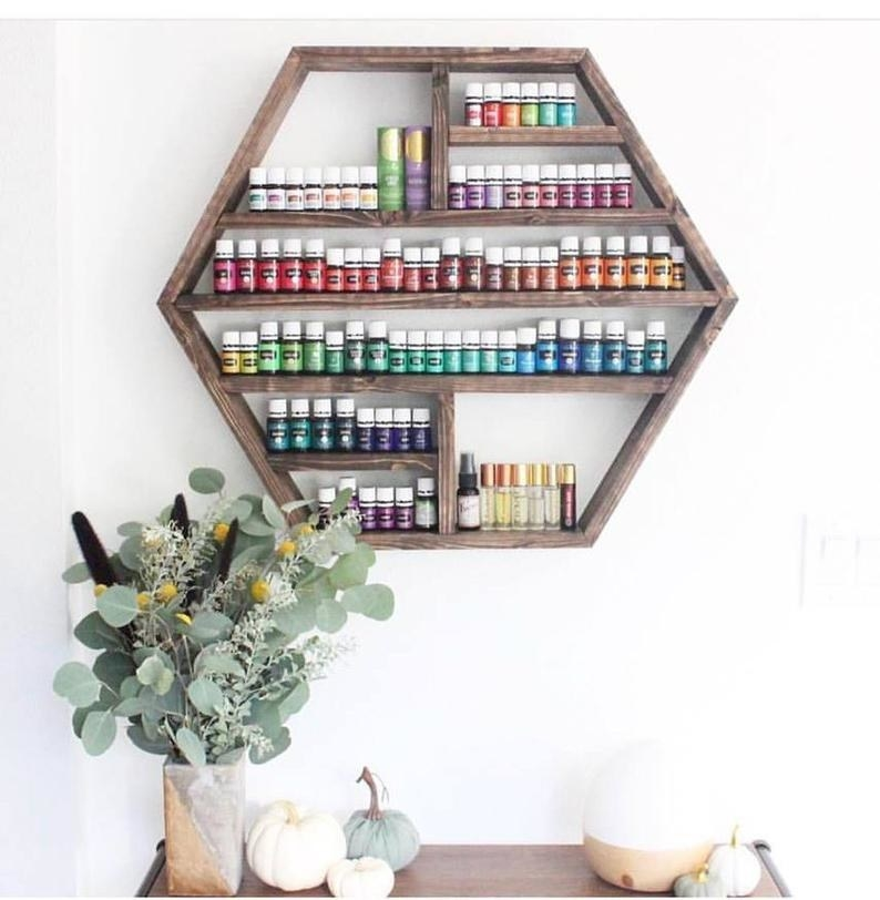 wood shelf shaped like a hexagon holding tons of essential oil bottles