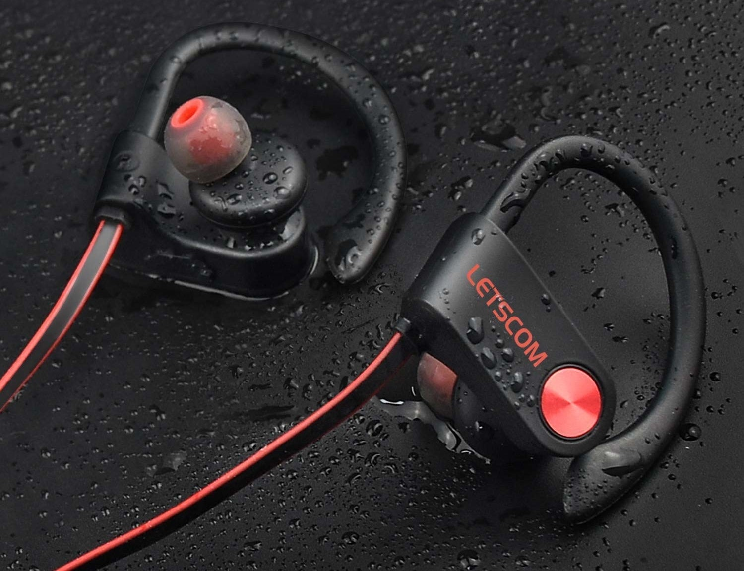 earbuds with over-ear pieces laying among droplets of water