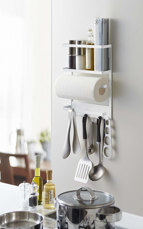 Magnetic organization rack hanging on side of fridge with kitchen utensils