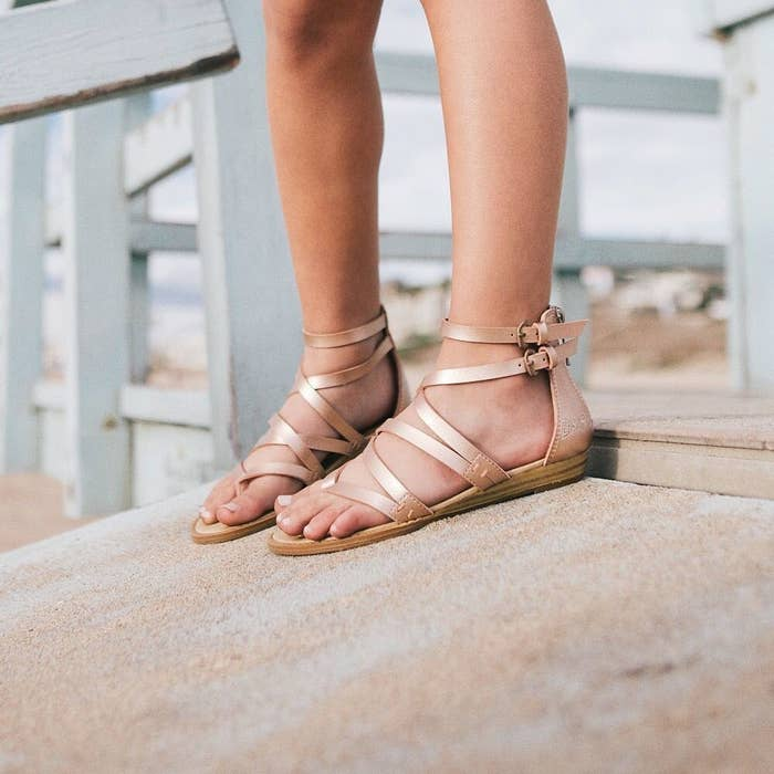person wearing rose gold color sandals in a beach-y setting