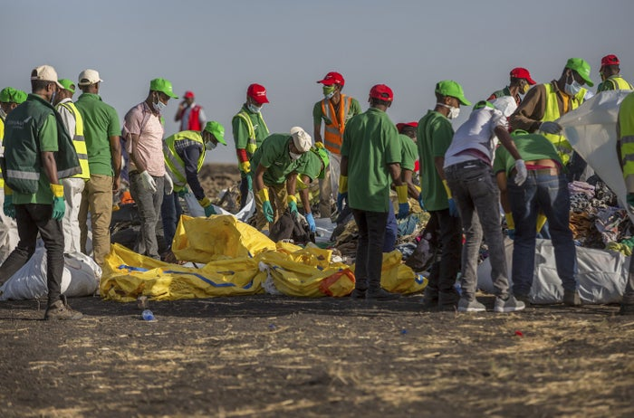 Workers collect clothes and other materials at the scene where the Ethiopian Airlines Boeing 737 Max 8 crashed shortly after takeoff.
