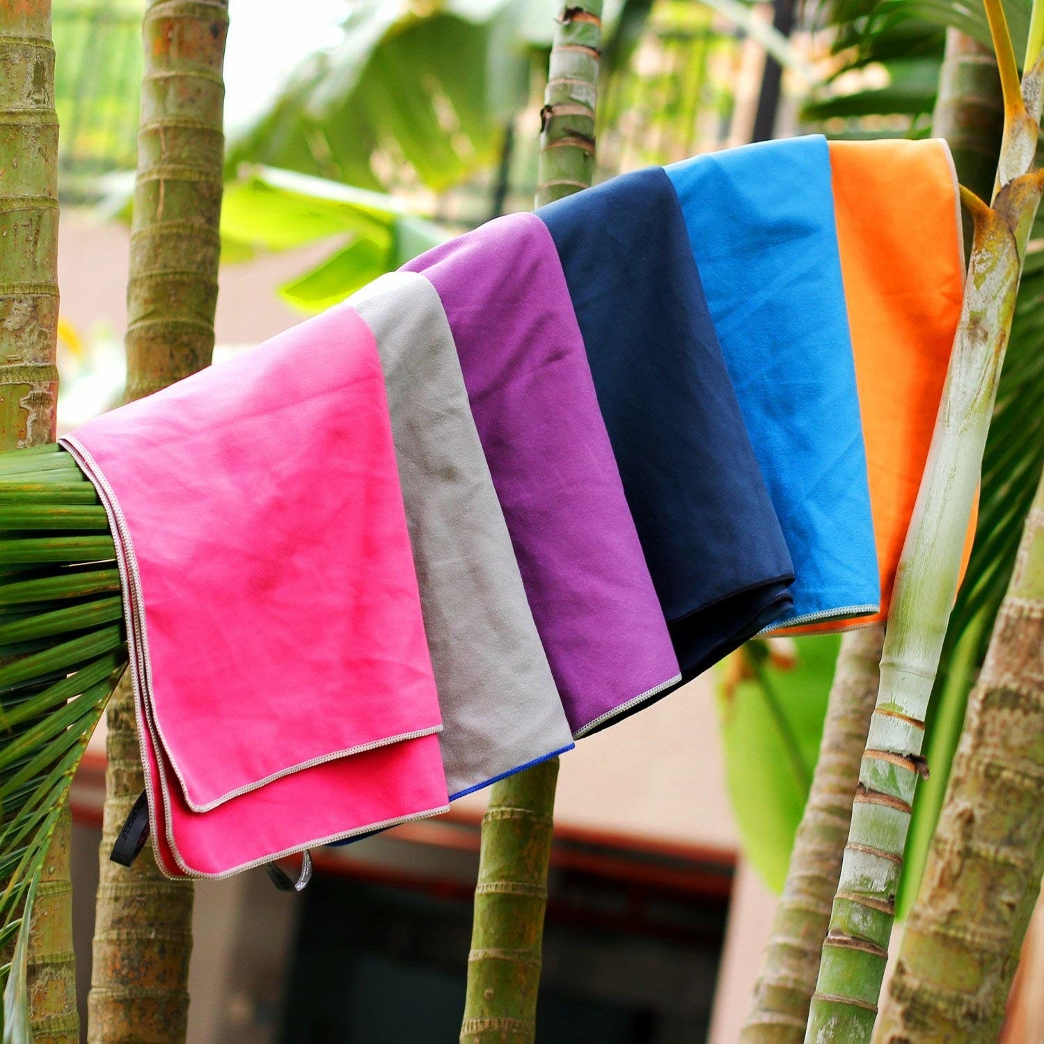 the towel in various colors hanging on a palm tree branch