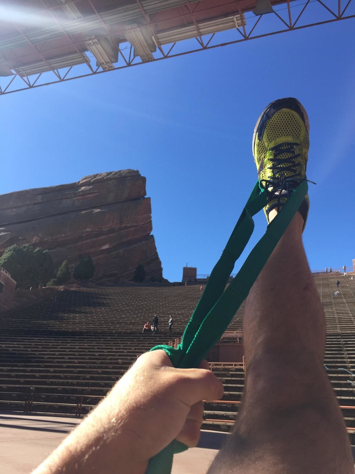 person stretching their right leg by gripping a green fabric strap around their foot