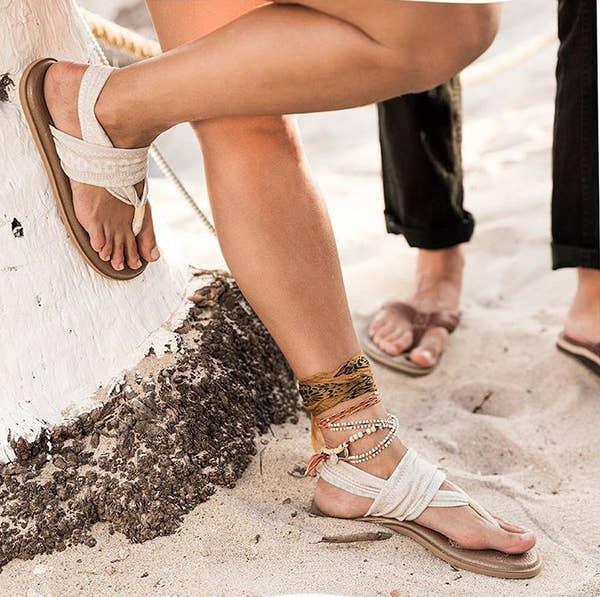 model wearing fabric sandals on beach