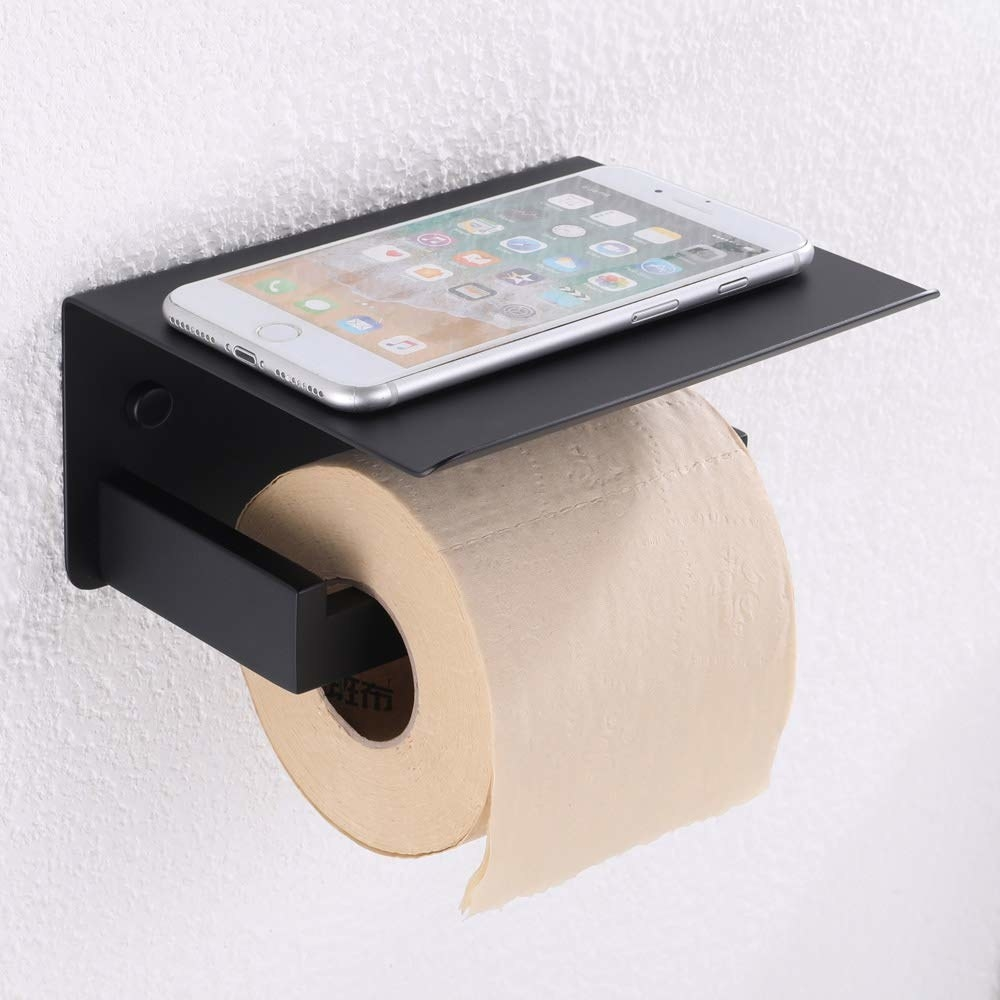 A toilet paper holder with a shelf on top