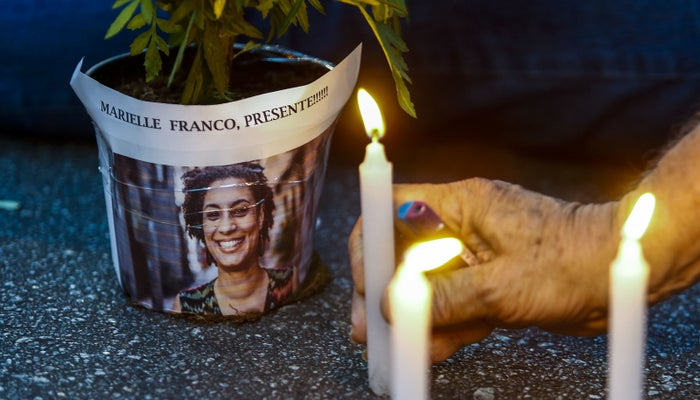 A man lights a candle during a rally against the killing of Marielle Franco in São Paulo in March 2018.