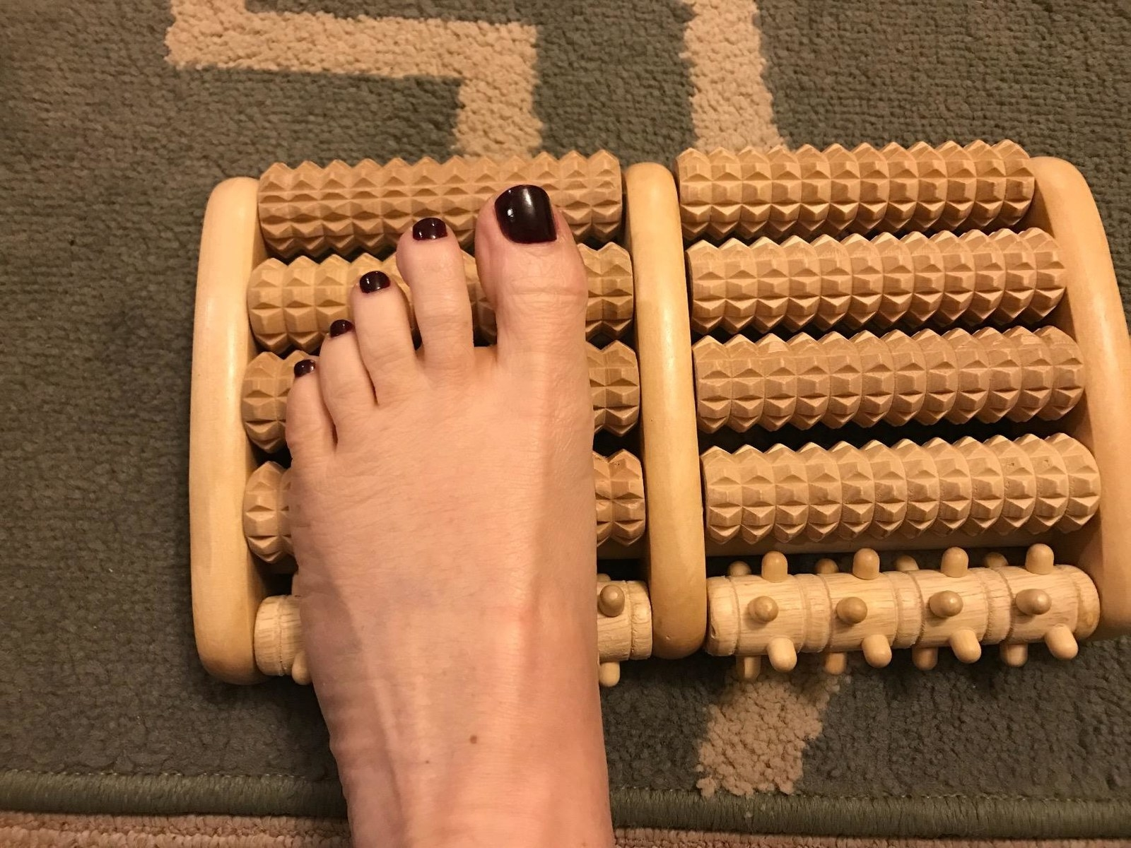 person's foot on the wooden massager's bumpy rollers