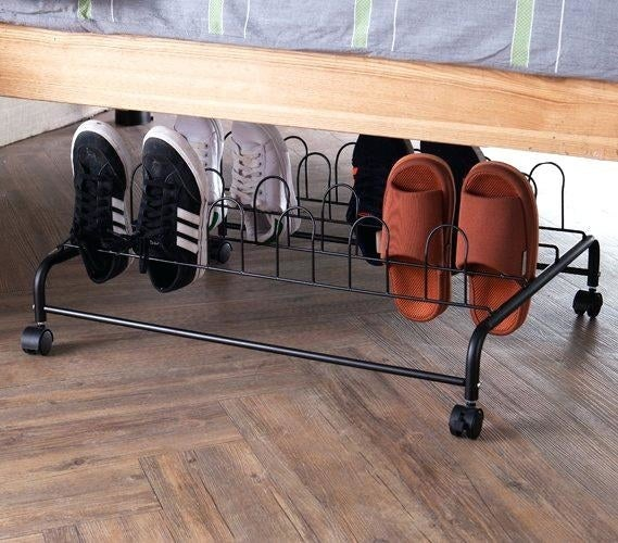 """Just remember to wheel it back under your bed when you're done! It holds 12 pairs of shoes and measures 26"""" x 36.25"""" x 10.25"""". Get it from Walmart for $34.92 (available in black and white)."""