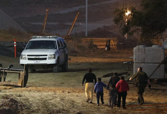 Migrants are escorted by a US Border Patrol agent as they are detained in San Ysidro, California.