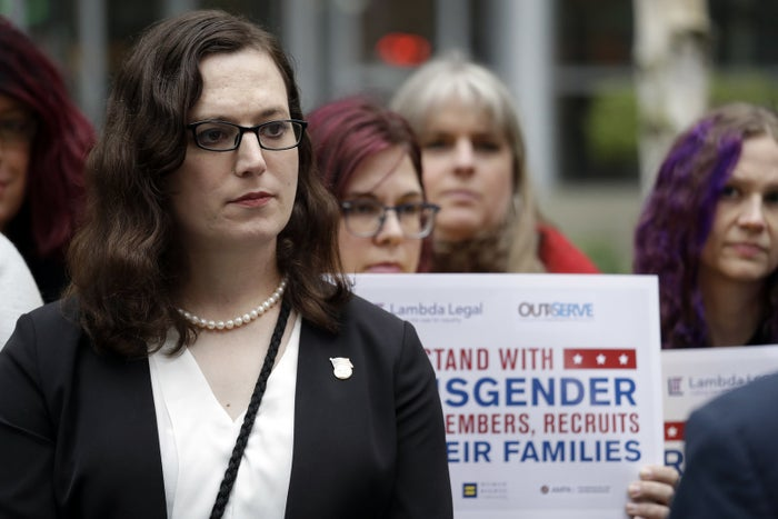 Cathrine Schmid, a trans staff sergeant, listens during a news conference in Seattle.