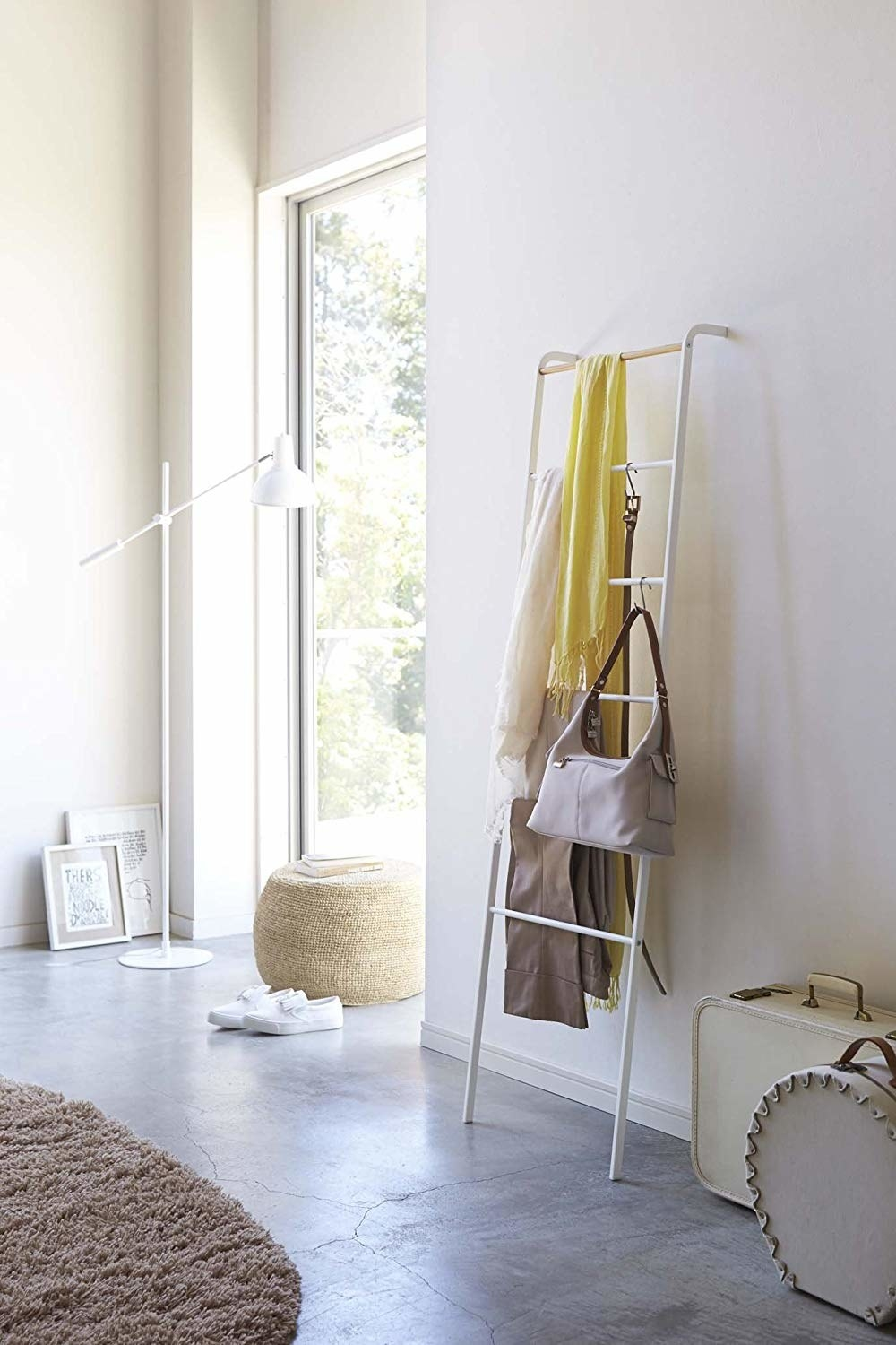 Leaning white ladder with scarves and purses hanging on it