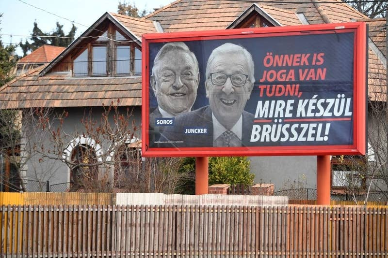 """A billboard featuring pictures of European Commission president Jean-Claude Juncker and Hungarian-born US investor and philanthropist George Soros. The slogan translates to: """"You too have a right to know what Brussels is preparing."""""""