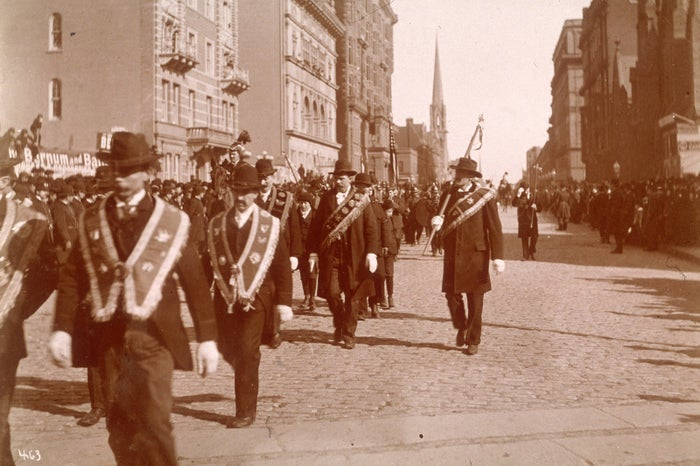 People march in the Saint Patrick's Day Parade in 1895. The steeple of the Central Presbyterian Church on 57th Street is in the distance.