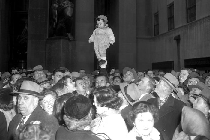 A small child is given the best view of the St. Patrick's Day parade, across the street from St. Patrick's Cathedral, circa 1940.