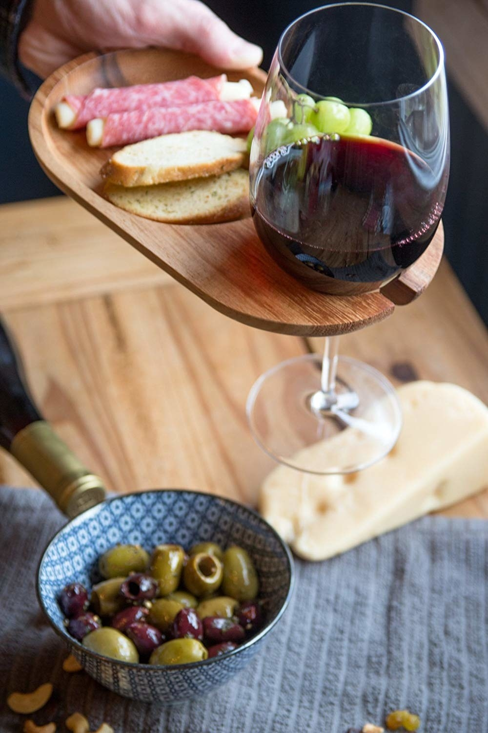 Wooden plate with built-in slot with wine glass hanging from it