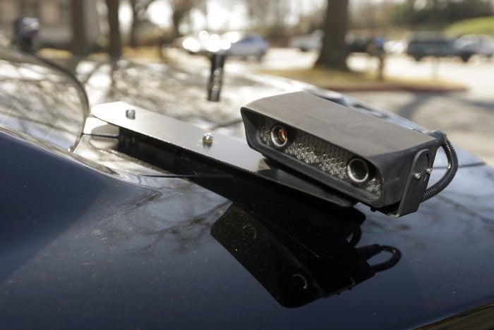 A camera is mounted near the rear window of a police car in Little Rock, Ark.