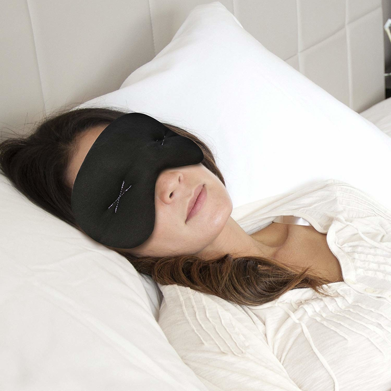 a person with the black compression eye mask on laying in bed