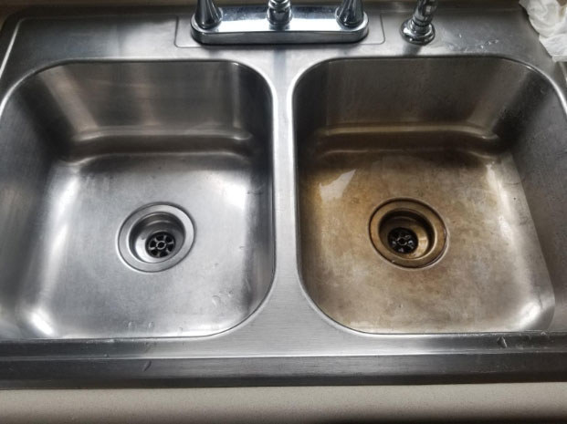 A reviewer photo of a double sink one where one side has been cleaned with the product and is shiny and new looking, and the other uncleaned side is rusty and worn looking