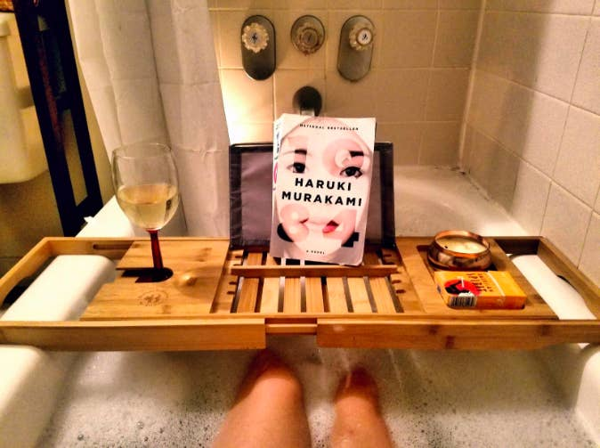 a customer review photo of the bath tray holding a book and glass of wine over a bubble bath