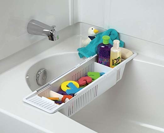 the bath organizer hanging over the tub and holding toys