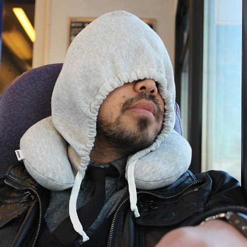 A model covering their face with the hoodie while using the pillow on a train