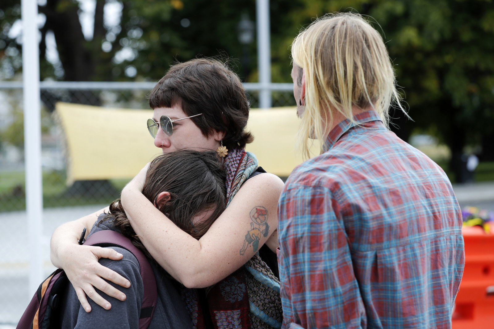 Mourners reacts as they pay their respects at a makeshift memorial outside Christchurch hospital.