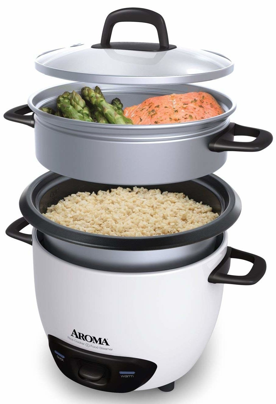 rice cooker with brown rice in the bottom and a steamer basket of salmon and asparagus on top of it