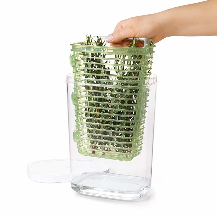hand lifting drainage basket full of herbs out of clear plastic body of keeper