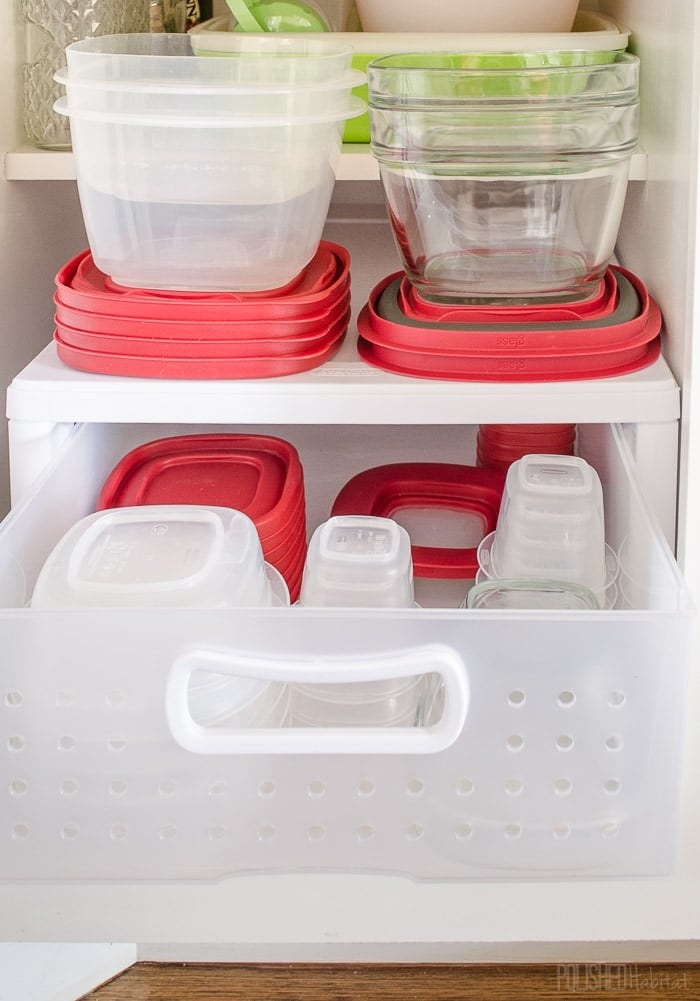 blogger's bottom cabinet with open white plastic drawer; plastic and glass storage containers are stacked on top of and within the drawer