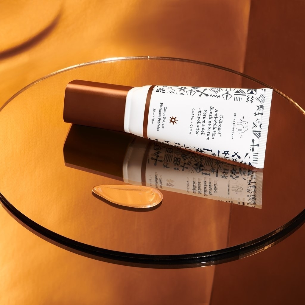 bottle of the serum next to a small puddle of it, showing the bronzy, shiny coloring