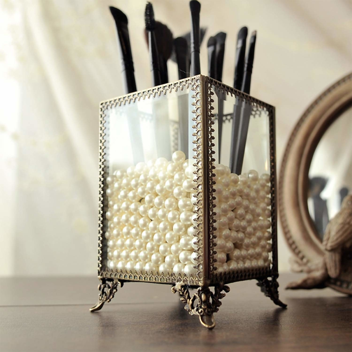 brass and glass container with pearls and makeup brushes