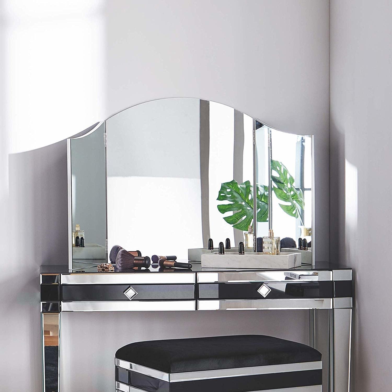 The hinged mirror set on top of a vanity