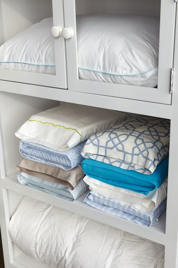 closet with sheet sets stored in pillowcases