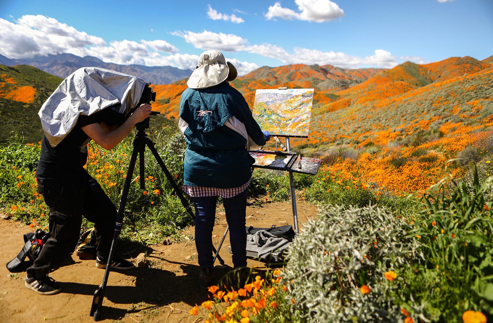 A man photographs a woman painting flowers, March 12.