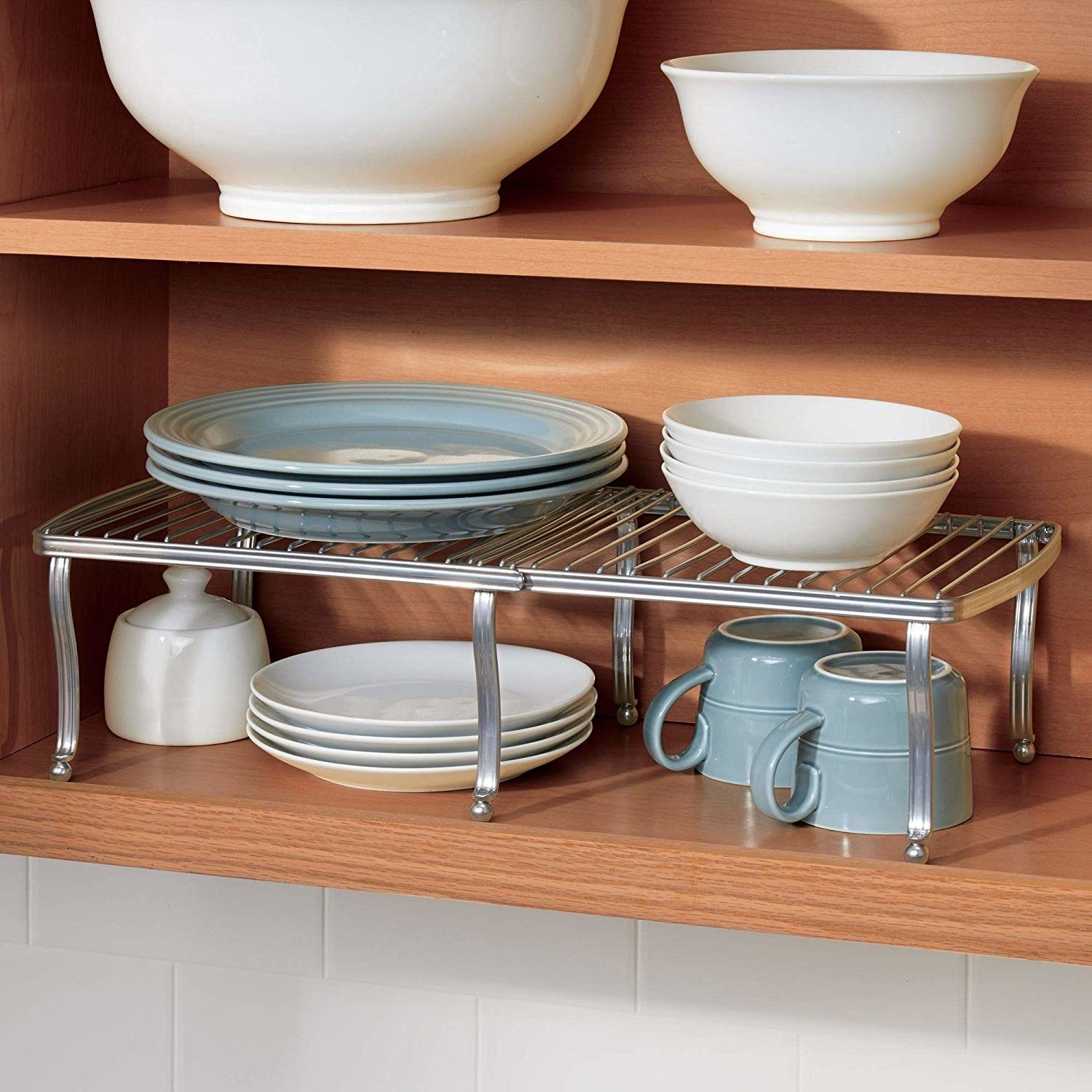 silver wire expanding shelves holding plates and bowls