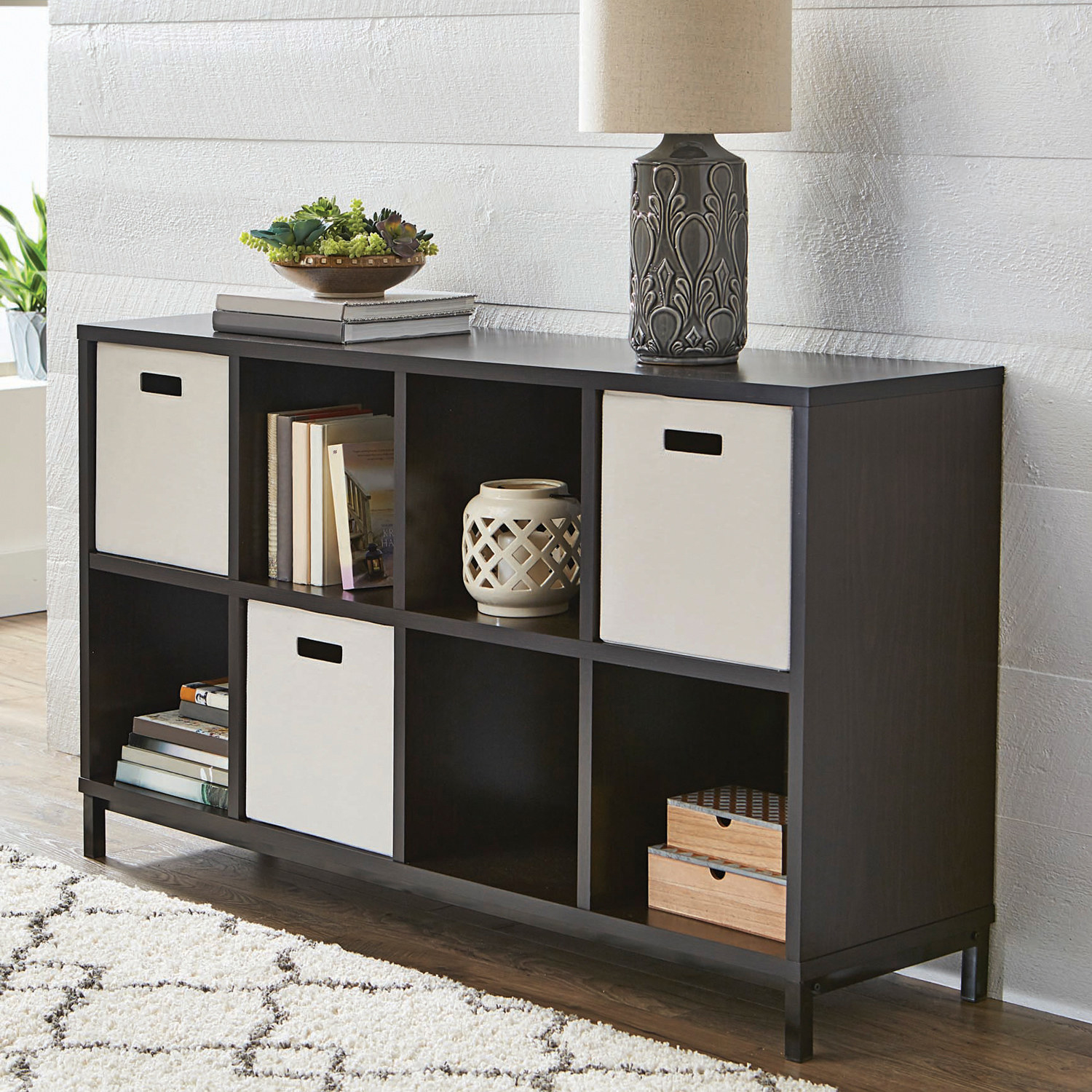 dark brown storage unit holding books, decorative boxes, lamp, and with three cubes turned into drawers